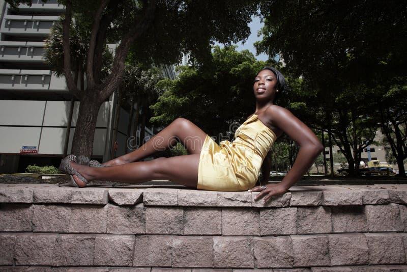 Frau, die in einem goldenen Kleid aufwirft lizenzfreie stockbilder