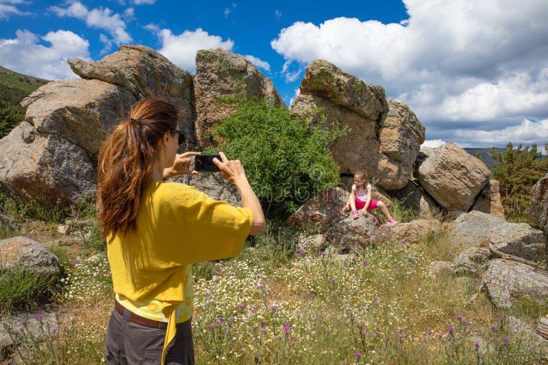 Frau, die einem kleinen Mädchen ein Foto mit Smartphone spielt in der Landschaft macht lizenzfreie stockfotos