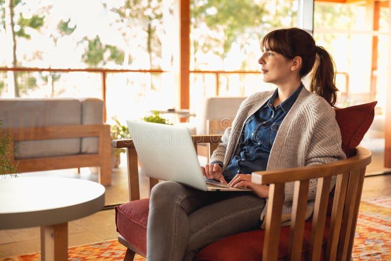 Frau, die an einem Laptop arbeitet lizenzfreie stockbilder