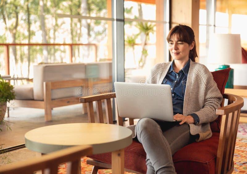 Frau, die an einem Laptop arbeitet lizenzfreie stockfotografie