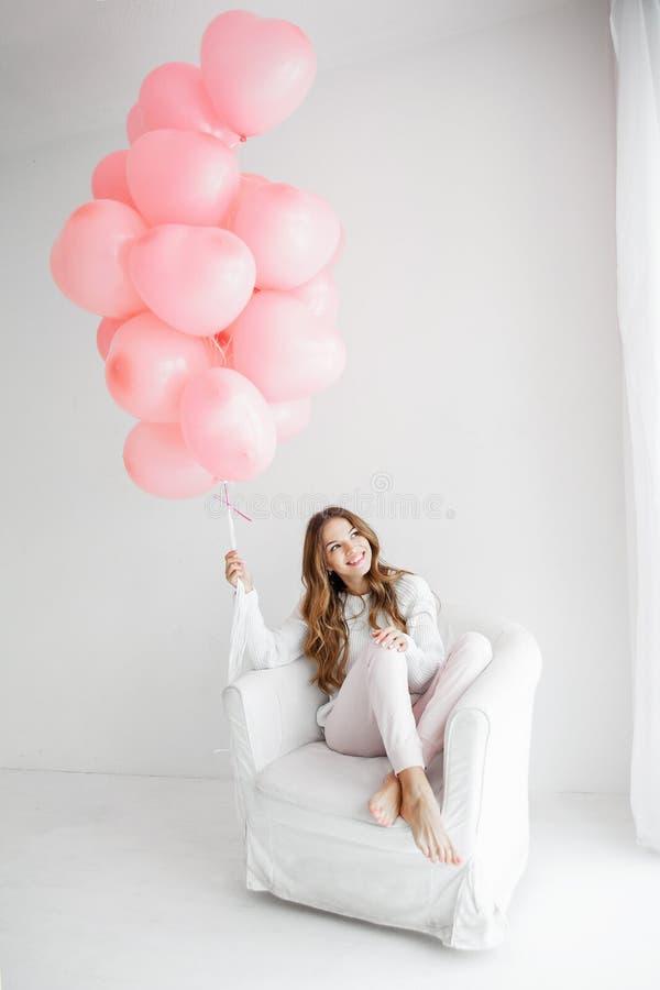 Frau, die in einem Lehnsessel sitzt und ein Bündel rosa Ballone hält stockbild