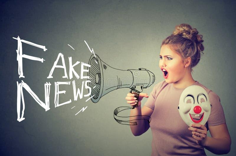 Frau, die in einem Megaphon verbreitet gefälschte Nachrichten schreit stockbild