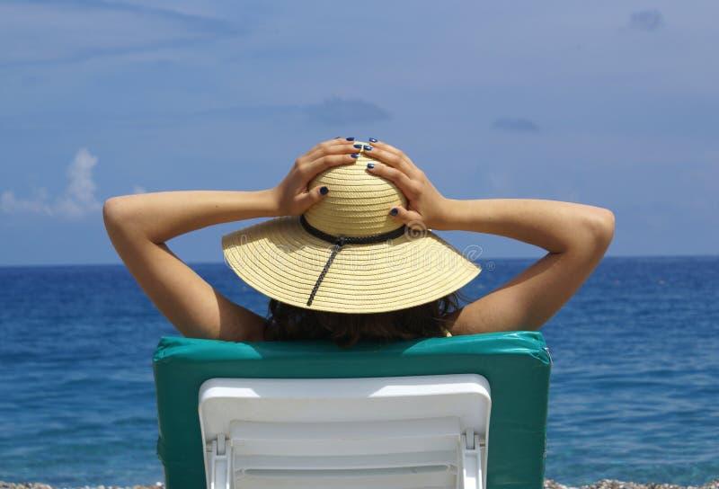 Frau, die in einem Plastikstuhl auf einem schönen ein Sonnenbad nimmt lizenzfreie stockfotografie