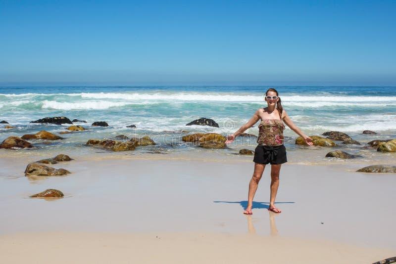 Frau, die an einem Strand steht stockfotografie