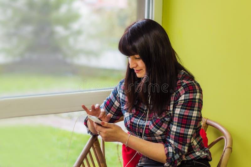 Frau, die in einem Stuhl mit einem Handy sitzt stockfotografie