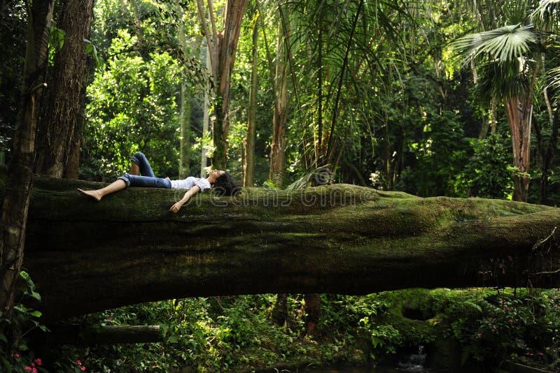 Frau, die in einem tropischen Wald sich entspannt lizenzfreie stockfotos