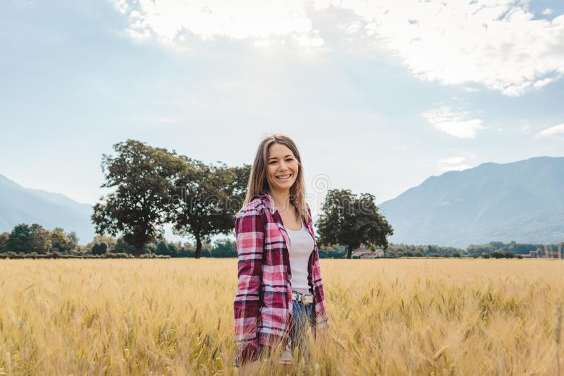 Frau, die in einem Weizen archiviert aufwirft stockbild