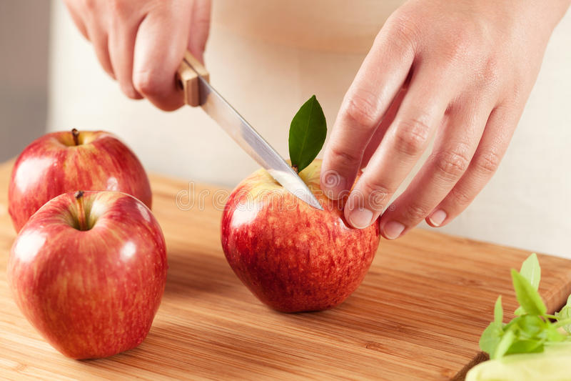 Frau, die einen Apfel schneidet lizenzfreies stockfoto
