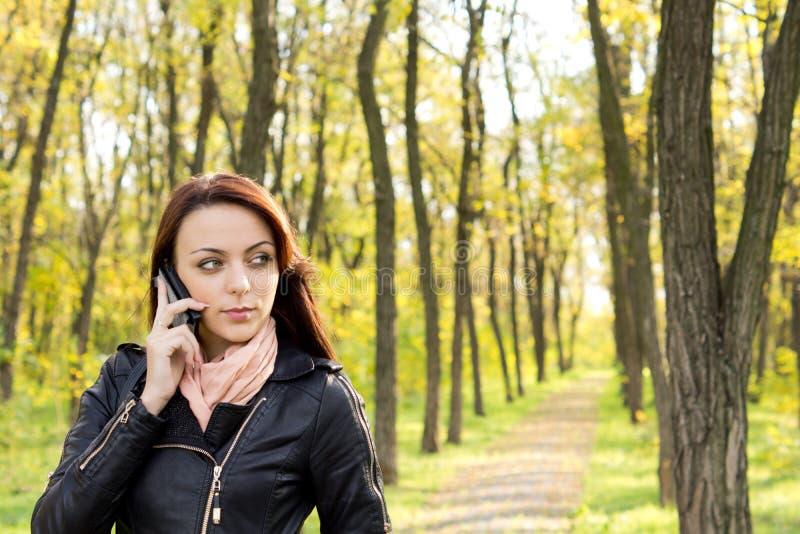 Frau, die einen Aufruf auf ihrem Mobile wartet lizenzfreies stockfoto