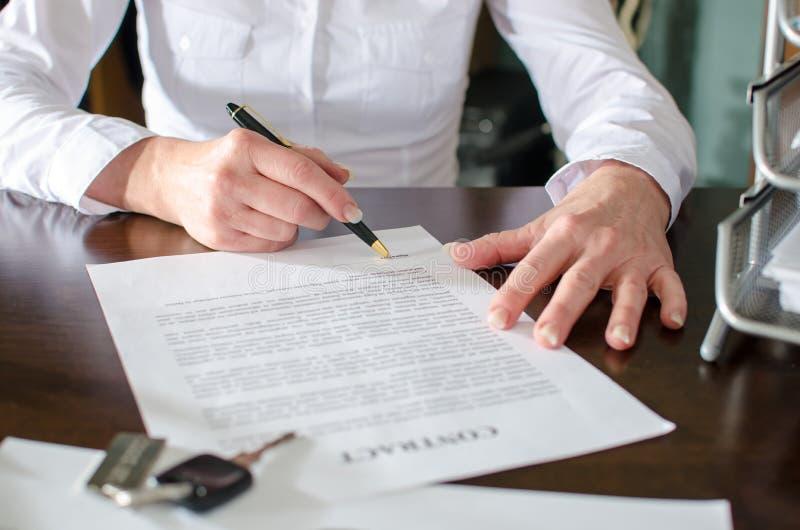 Frau, die einen Autokaufvertrag unterzeichnet stockfoto