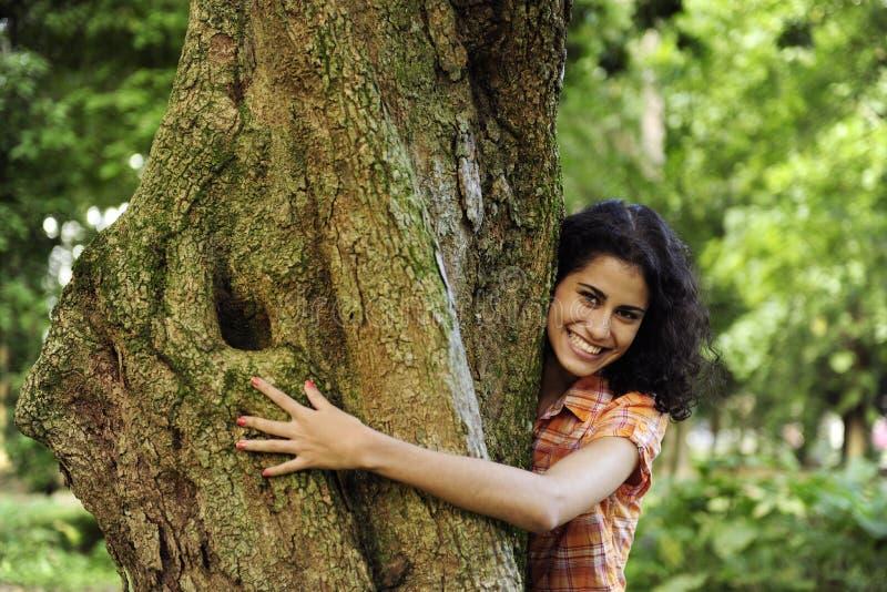 Frau, die einen Baum im Wald umarmt stockfotos