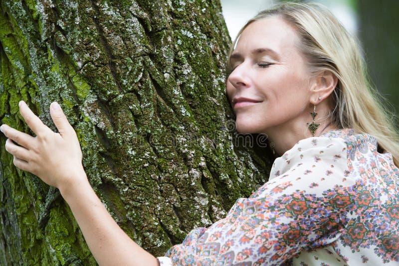 Frau, die einen Baum umarmt lizenzfreies stockbild