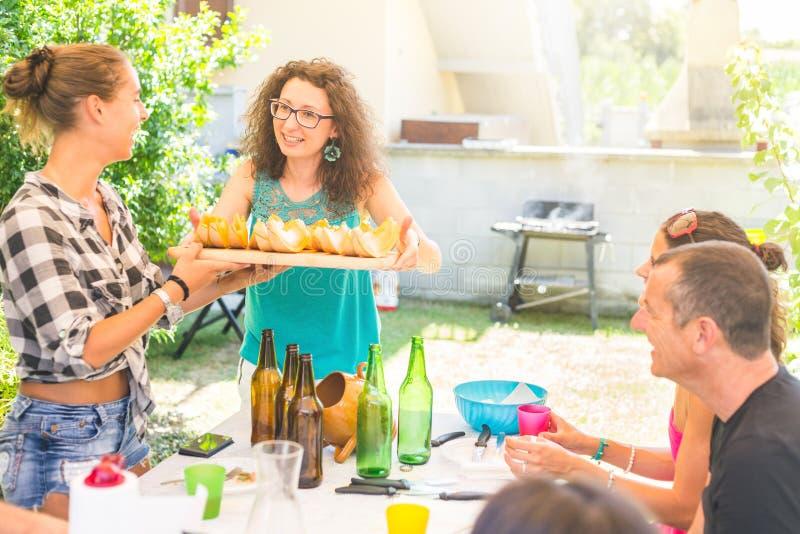 Frau, die einen Behälter mit Scheiben der Melone hält lizenzfreie stockfotos