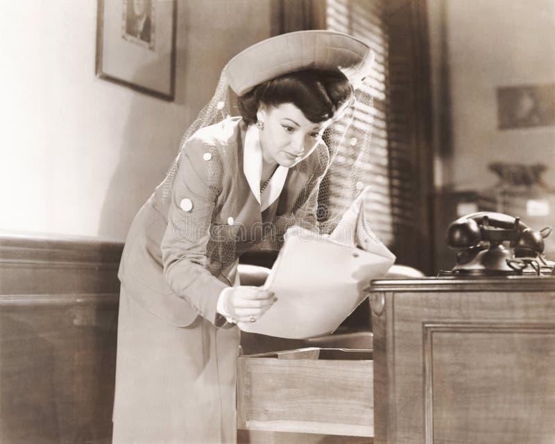 Frau, die einen Blick an den Dokumenten im Büro schleicht lizenzfreies stockbild