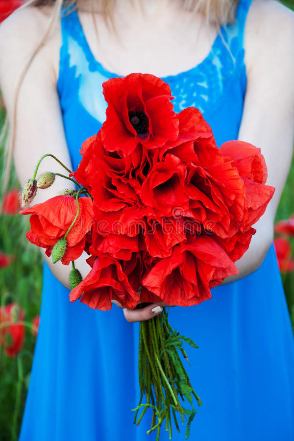 Frau, die einen Blumenstrauß des Saat-Mohns hält lizenzfreie stockbilder