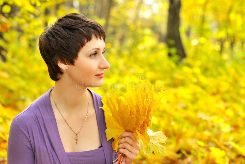 Frau, die einen Blumenstrauß von Ahornblättern in einem Herbstpark hält stockbilder