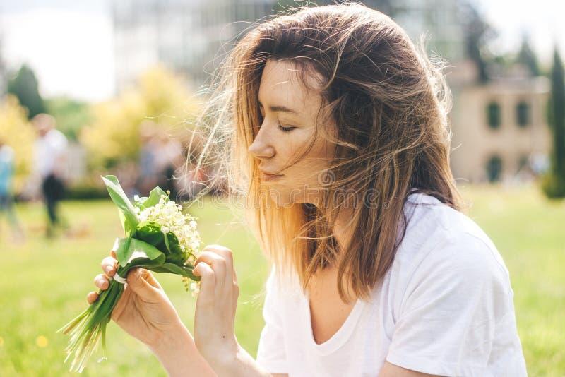 Frau, die einen Blumenstrauß von lilly von Talblumen hält stockfoto