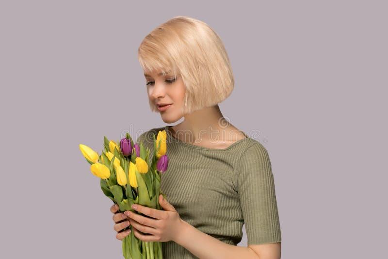 Frau, die einen Blumenstrauß von Tulpen hält stockfotos