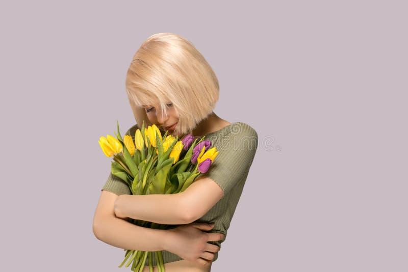 Frau, die einen Blumenstrauß von Tulpen hält lizenzfreie stockfotos