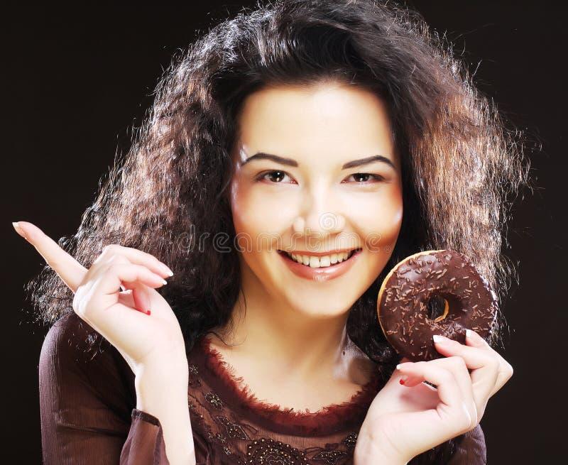 Frau, die einen Donut hält stockbilder