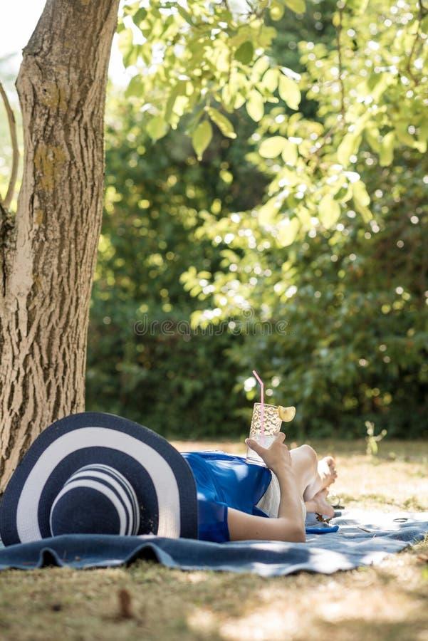 Frau, die einen entspannenden Tag im Garten liegt im Schatten O verbringt lizenzfreies stockbild