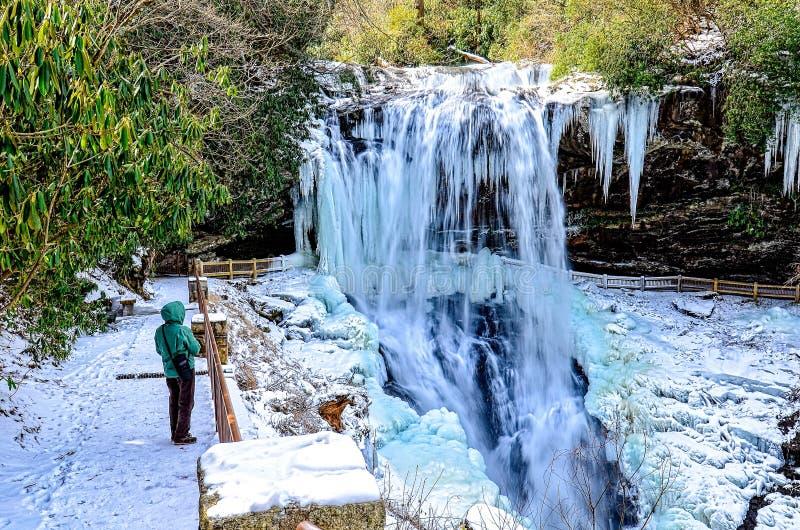Frau, die einen gefrorenen Wasserfall betrachtet lizenzfreie stockfotografie