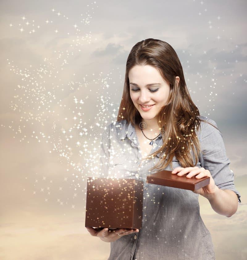 Frau, die einen Geschenk-Kasten öffnet stockfoto