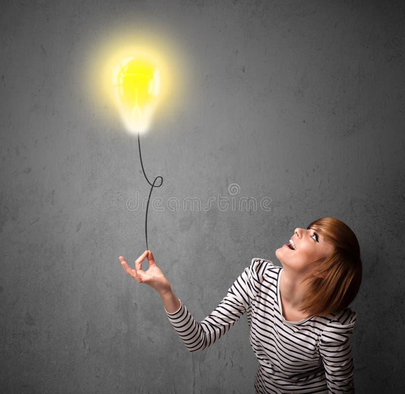 Frau, die einen Glühlampenballon hält lizenzfreie stockfotografie