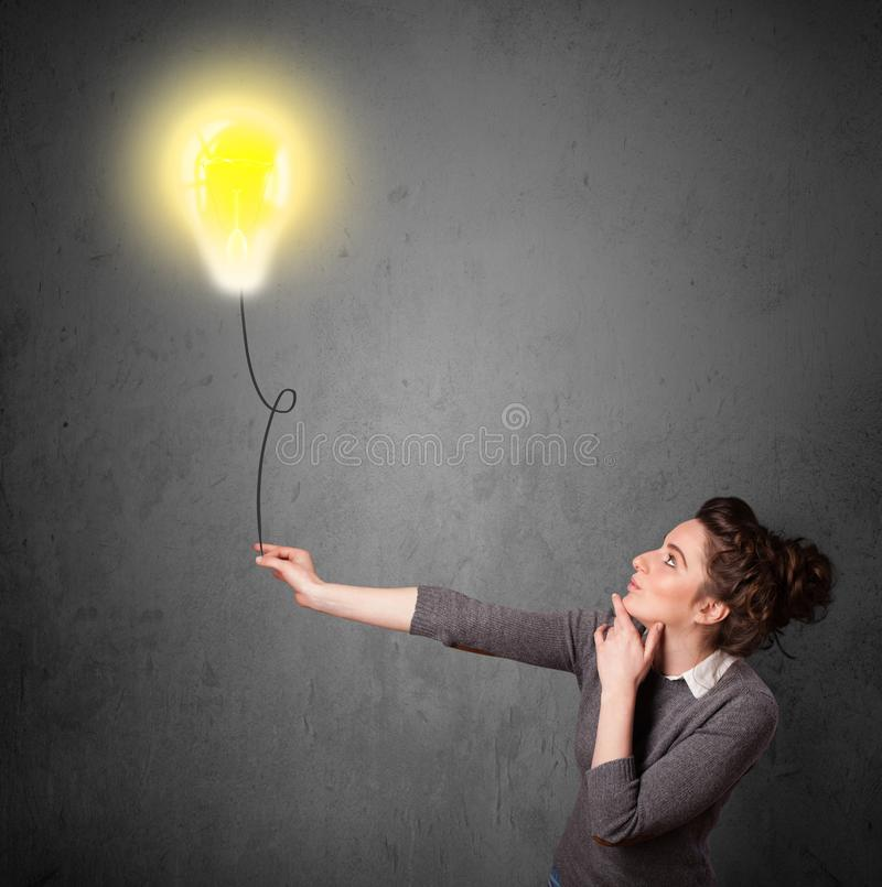 Frau, die einen Glühlampenballon hält lizenzfreie stockfotos