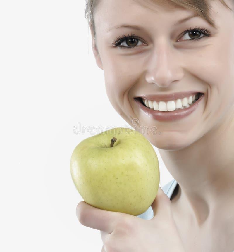 Frau, die einen grünen Apfel anhält lizenzfreie stockfotos