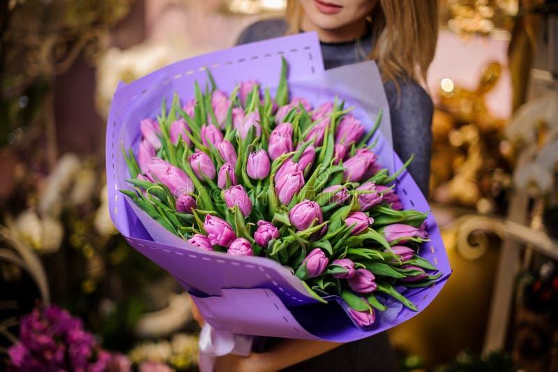 Frau, die einen großen Blumenstrauß von purpurroten Tulpen hält lizenzfreie stockfotos