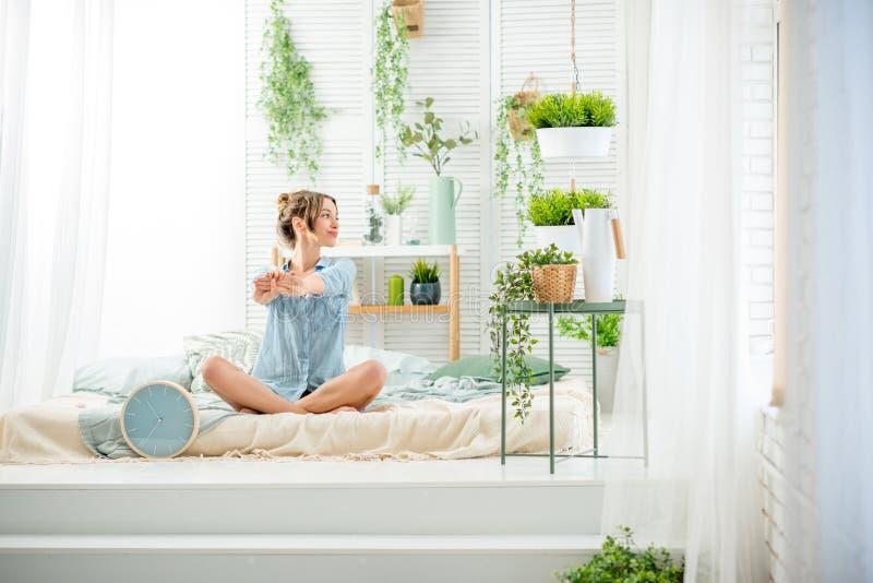Frau, die einen guten Morgen im Schlafzimmer hat stockfotografie