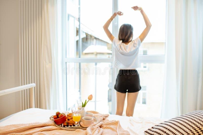 Frau, die einen guten Morgen am Schlafzimmer hat stockfotografie