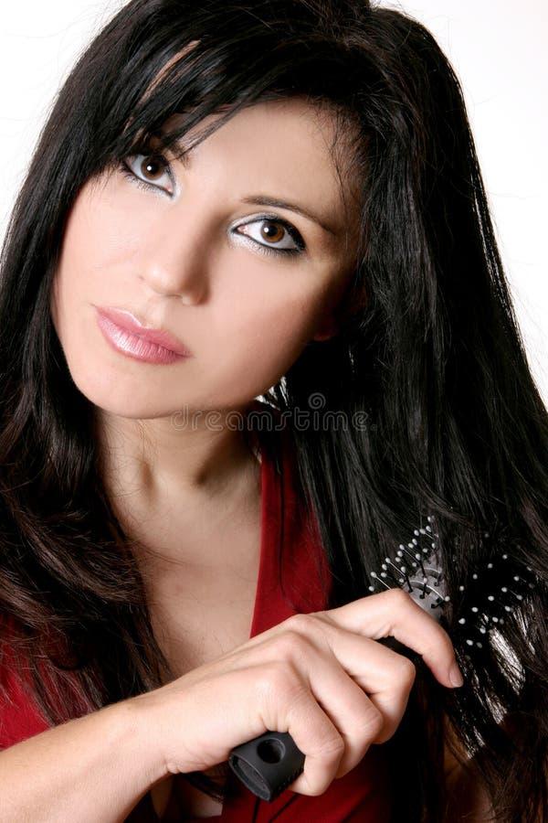 Frau, die einen Haarpinsel verwendet stockfotos