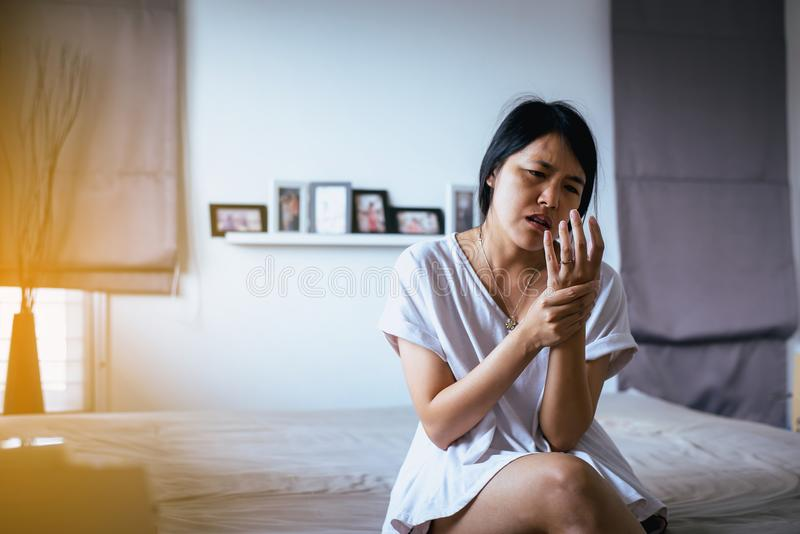 Frau, die einen Hals ihre Hand, weibliches Gefühl erschöpft und schmerzlich auf Schlafzimmer hat stockfoto