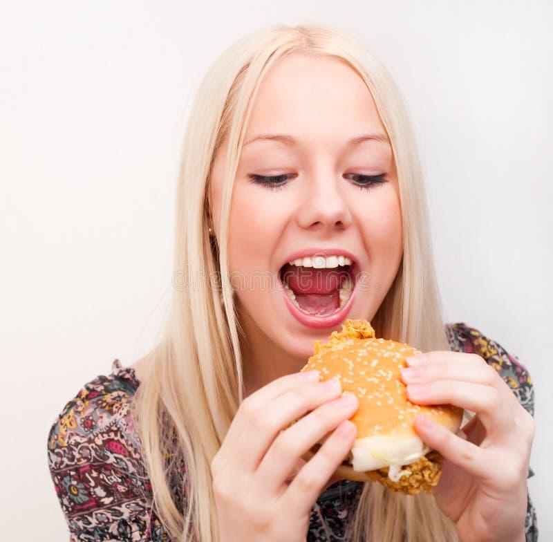 Frau, die einen Hamburger isst stockfoto
