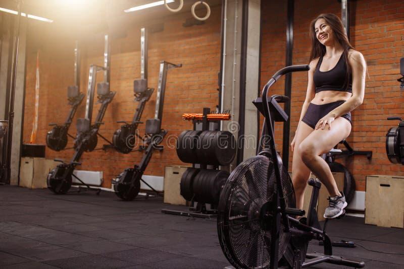Frau, die einen Hometrainer in der Turnhalle reitet geeignetes Mädchen, das Herz Training auf Fahrrad tut lizenzfreies stockfoto