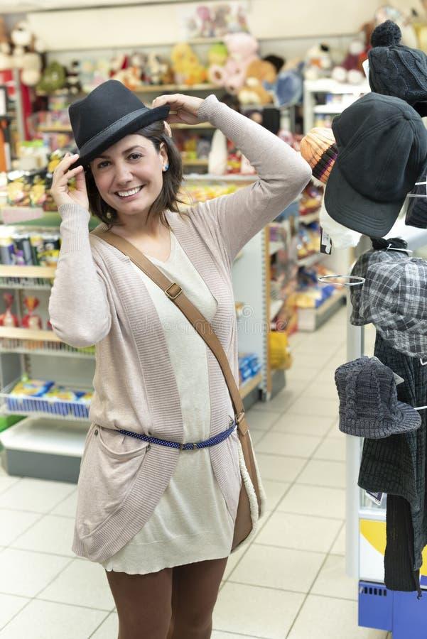 Frau, die einen Hut versucht lizenzfreies stockbild