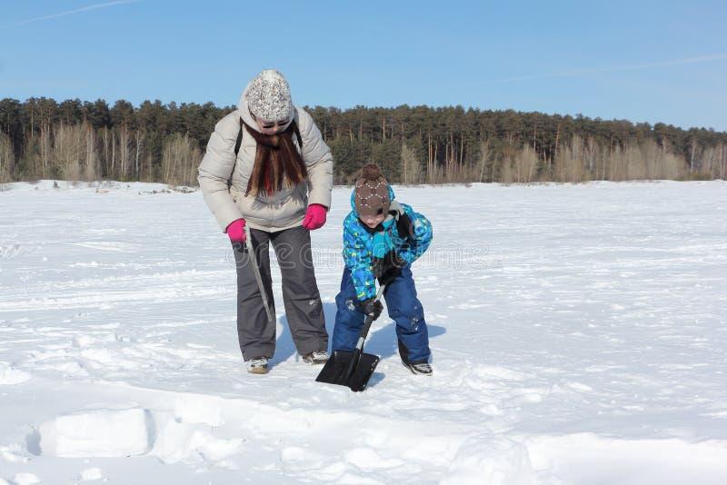 Frau, die einen Jungen unterrichtet, einen Schneeblock zu graben, um einen Iglu, Nowosibirsk, Russland zu errichten stockfotografie
