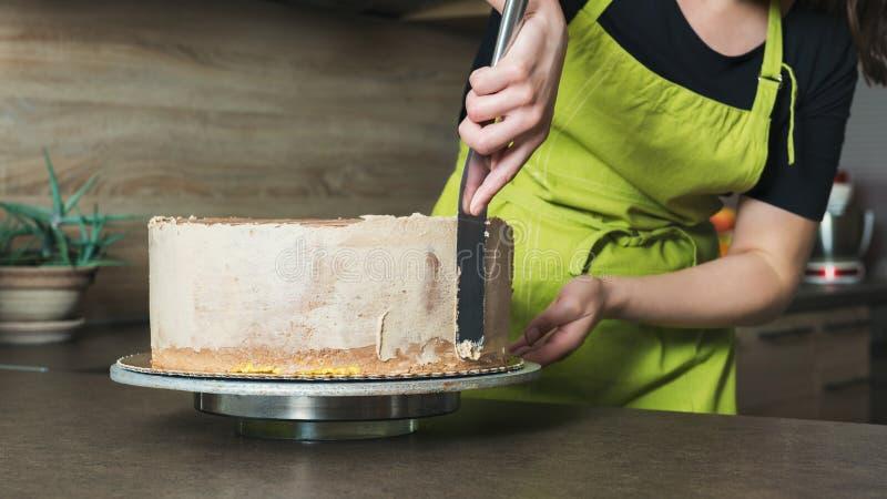 Frau, die einen köstlichen überlagerten Schwammkuchen mit SchokoladenEiscreme verziert stockfotos