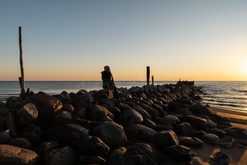 Frau, die einen kalten Frühlingssonnenuntergang an einem Flusssteinstrand nahe der Ostsee genießt lizenzfreie stockbilder