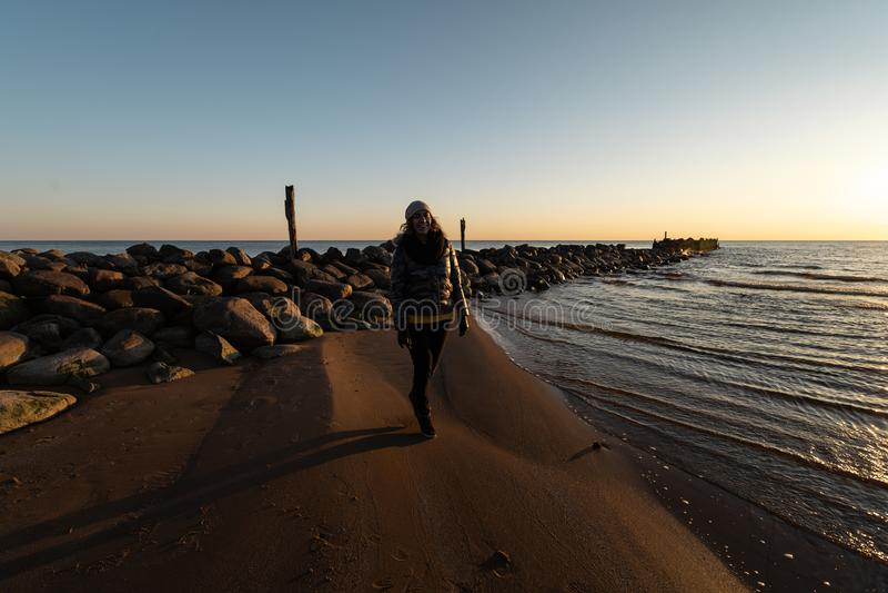 Frau, die einen kalten Frühlingssonnenuntergang an einem Flusssteinstrand nahe der Ostsee genießt stockfotos