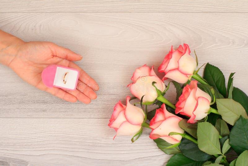 Frau, die einen Kasten mit goldenem Ring in der Hand mit Blumen auf dem Hintergrund hält stockbild