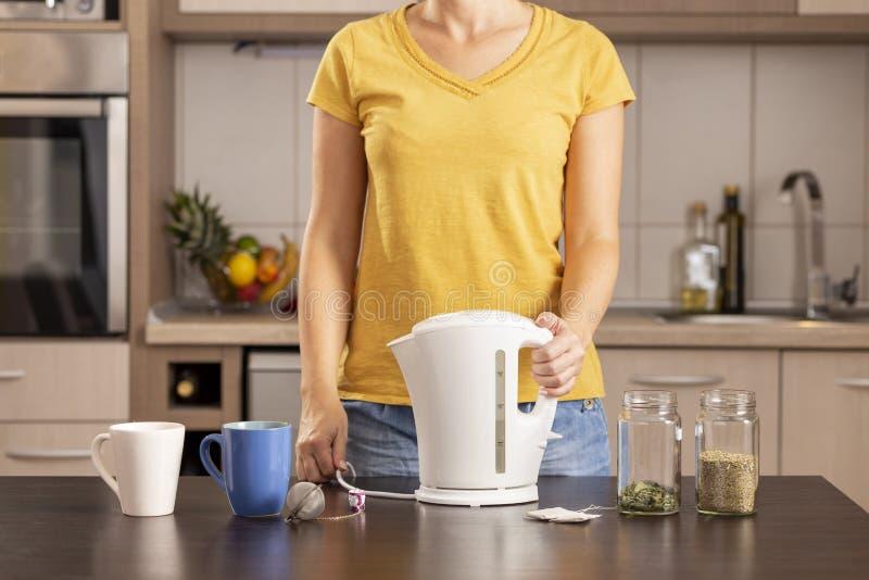 Frau, die einen Kessel, Tee machend hält stockfotos