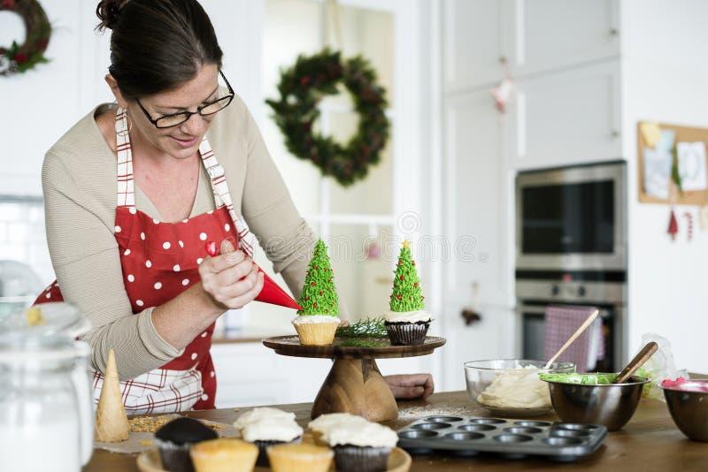 Frau, die einen kleinen Kuchen hoilday verziert lizenzfreies stockfoto
