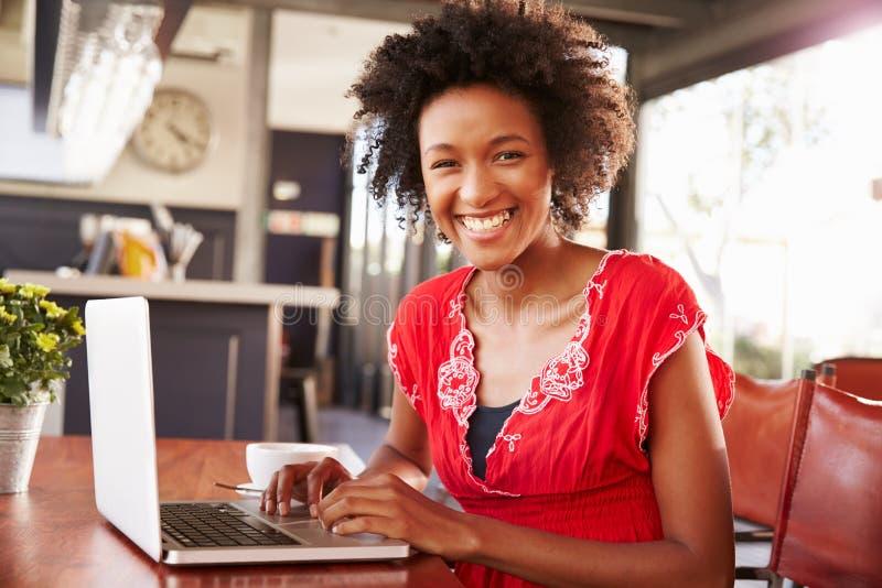 Frau, die einen Laptop an einer Kaffeestube, Porträt verwendet stockfotografie