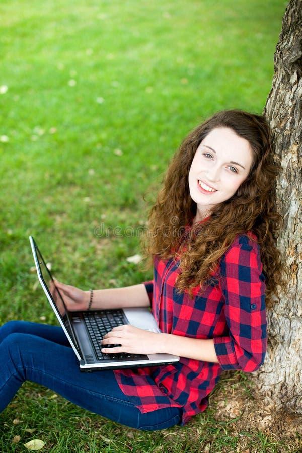 Frau, die einen Laptop unter einem Baum verwendet stockbild