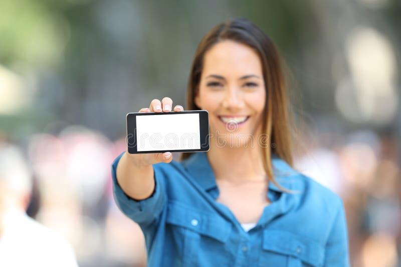 Frau, die einen leeren horizontalen Telefonschirm zeigt lizenzfreie stockfotografie