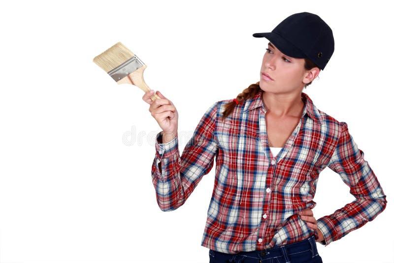 Frau, die einen Malerpinsel hält stockfoto