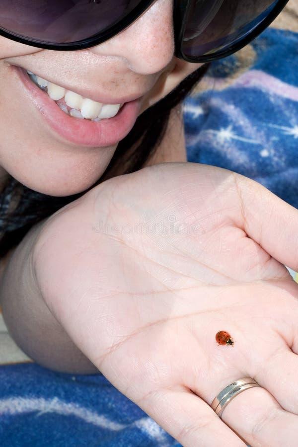 Frau, die einen Marienkäfer anhält stockbilder